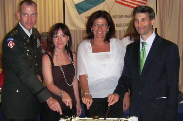 Lt. Col. Steven Cade (left), commander of U.S. Army Garrison Livorno, Italy; Daniela DiPierro, vice consul at the U.S. Consulate in Naples; Capt. Regent Rosa Zafferani, San Marino-American Friendship Association regent; and Paolo Berardi, San Marino-American Friendship Association president celebrate, 30 years of American-Sammarinese friendship at a cake cutting ceremony celebrating the release of a San Marino friendship stamp.