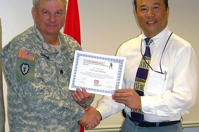 Terry Bautista, Europe DistrictAca,!a,,cs chief of engineering and construction division congratulates Lt. Col.Gary Osborne for completeing the BCDC.