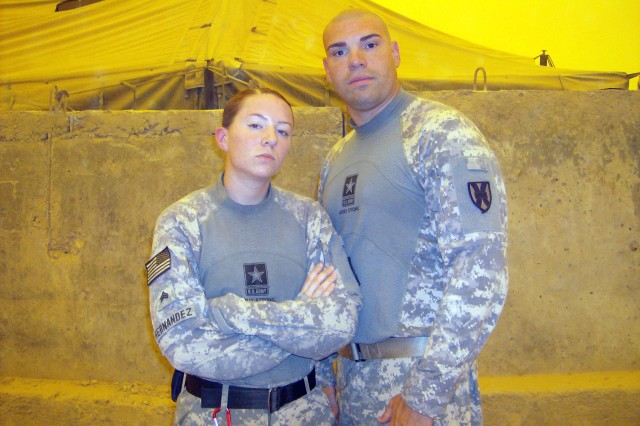 Sgt. Shannon B. Hernandez (left) and Staff Sgt. Jeffery T. Toniatti (right) demonstrate the new army combat shirt. The arms act as the outer sleeve on a normal uniform and the middle of the shirt acts as an undershirt.