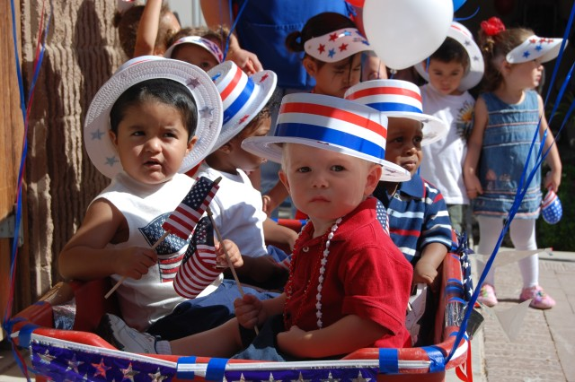 Toddlers from the Fort Bliss Main Child Development Center parade down Haan Road in a decorated wagon during the Red, White and Blue parade to honor the Army's 233rd Birthday.