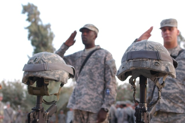 Soldiers salute the memorial honoring Staff Sgt. Alex Jimenez and Spc. Byron Fouty at the MND-C Headquarters in Baghdad during a memorial ceremony July 21.
