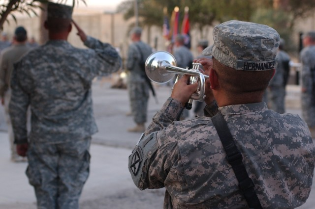 "A bugler plays ""Taps"" in remembrance of Staff Sgt. Alex Jimenez and Spc. Byron Fouty at the MND-C Headquarters in Baghdad during a memorial ceremony July 21."