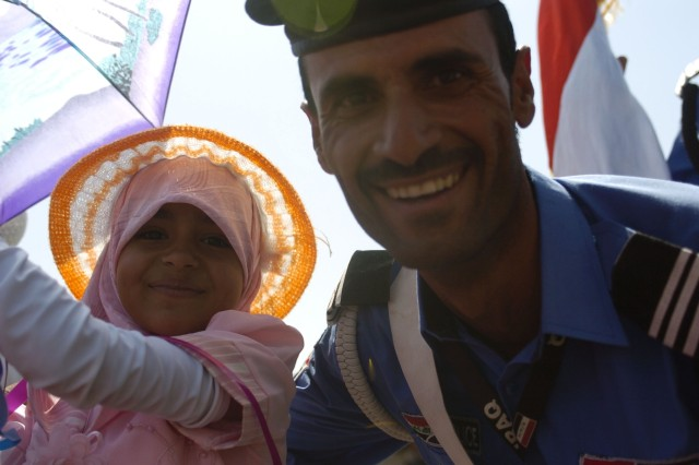 An Iraqi Policeman smiles with his daughter in celebration of the Najaf International Airport inauguration July 20.