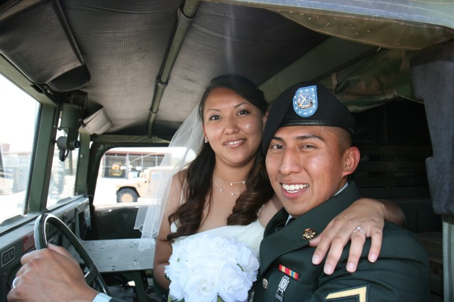"""PHOENIX - Newlyweds Pvt. Brandon and Charity Manygoats sit in the front seat of one of the unit humvees. The humvee was their """"just married"""" chariot following their unit-thrown wedding."""