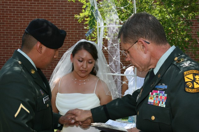 PHOENIX - Newlyweds Pvt. Brandon and Charity Manygoats hold hands as Chaplain (Col.) Charles South blesses the couple during the ceremony. The wedding was thrown by Manygoats' unit so the two would not have to wed at the local courthouse.