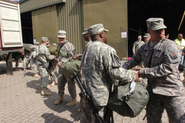 Soldiers from U.S. Army Europe's 16th Sustainment Brigade load duffle bags onto a trailer at the Deployment Processing Center at Rhine Ordnance Barracks in Kaiserslautern, Germany as the unit deployed to Iraq July 19.