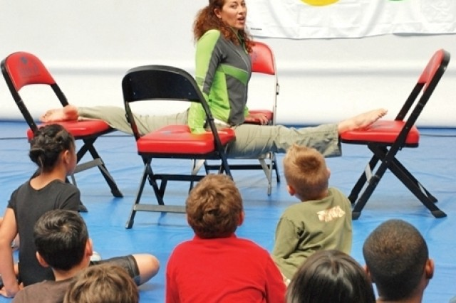 U.S. Army Garrison Wiesbaden, Germany, youths look on as Nathalie Bartleson, a 1996 Olympic gold medalist in synchronized swimming, demonstrates her flexibility during a session in the Wiesbaden Fitness Center June 27.
