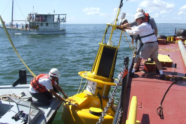 Corps of Engineers' Peter Jeffers (on skiff boat), NOAA Oceanographer Doug Wilson, along with Corps Crewmen Stan Caldwell and Glen Boykin, maneuver the smart buoy to a position directly on top of the nautical global coordinates.