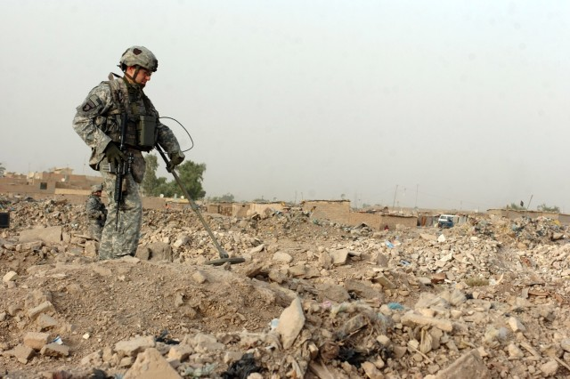 Sgt. Victor Faggiano, a native of Manchester, N.H., patrols a field of trash using a metal detector to search for possible enemy caches in northern Ghazaliyah, Iraq, July 10, 2008.