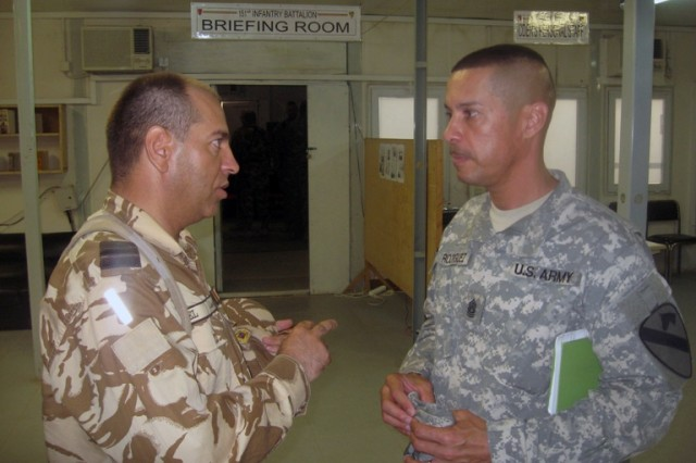 Romanian Command Sergeant Major Constantin Ionel, 151st Inf. Bn. command sergeant major, speaks with Command Sgt. Maj. Edwin Rodriguez, 4th BCT, 1st Cav. Div., during a coordination meeting between the units July 18.