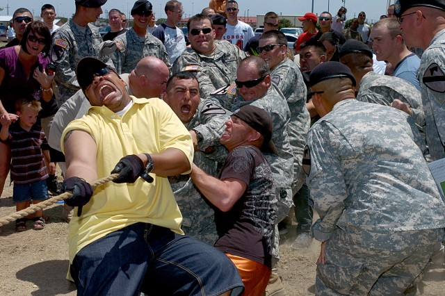 "Troop C, ""Crazy Horse"" puts up a fight against D, Forward Support Company's ""Defenders,"" during the tug-o-war competition and would later take down the victory during 4th Squadron, 9th Cavalry Regiment, 2nd Brigade Combat Team, 1st Cavalry's family day beside their squadron headquarters July 17."