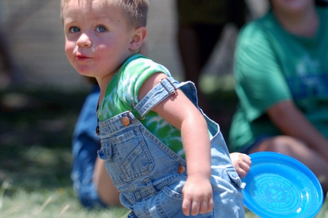 Nathan Hawbaker, 2, plays catch with his father Sgt. David Hawbaker, of Headquarters and Headquarters Troop, during the 4th Squadron, 9th Cavalry Regiment, 2nd Brigade Combat Team, 1st Cavalry's family day beside their squadron headquarters July 17.
