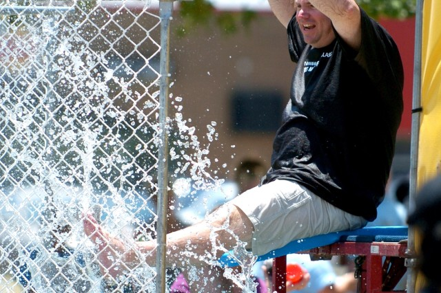 First Sgt. Carl Lay, Troop C's first sergeant from Dallas, Texas, taunts while in the dunking booth during the 4th Squadron, 9th Cavalry Regiment, 2nd Brigade Combat Team, 1st Cavalry's family day beside their squadron headquarters July 17.