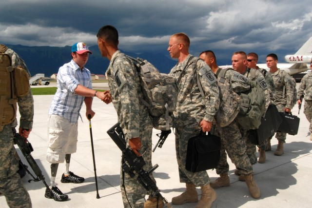 Spc. Jesse A. Murphree, Destined Company, 2nd Battalion, 503rd Infantry Regiment (Airborne), greets his 173rd Airborne Brigade Combat Team comrades returning from deployment in Afghanistan, on the flight line at Aviano Air Base, Italy, July 22. Murphree lost his legs in an improvised explosive device attack in the Korengal Valley, near Ali Abad, Afghanistan, Dec. 27, 2007, and has been undergoing treatment at the Walter Reed Army Medical Center.
