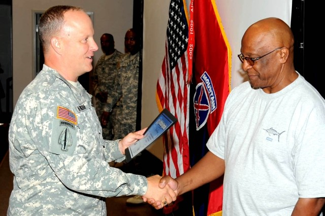 Col. Kevin Mangum, division rear commander, left, honors Robbie Robinson for his efforts during Fort Drum's recent Centennial celebration.