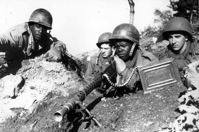 Fighting with the 2nd Infantry Division north of the Chongchon River, Sgt. 1st Class Major Cleveland, weapons squad leader, points out a North Korean position to his integrated machine-gun crew Nov. 20, 1950.