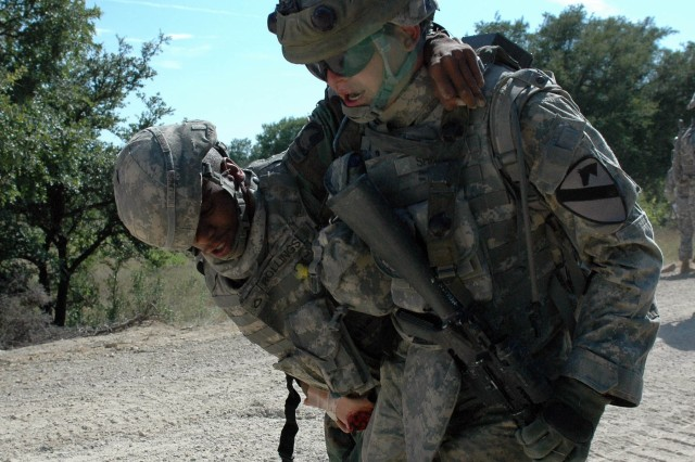 """Pfc. Timothy Rollings (left), with A Company, 215th Brigade Support Battalion, 3rd Brigade Combat Team, 1st Cavalry Division from Desoto, Texas and Pvt. Jordan Sharp (right), from B Company, 3rd Battalion, 8th Cavalry Regiment from Eaton Rapids, Mich., participate in a react to fire and traumatic first aid training simulation on Fort Hood July 21. This exercise is part of a two week event on Fort Hood conducted by """"Greywolf"""" Soldiers designed to simulate their upcoming deployment to Iraq and to prepare the troops for real life situations they may encounter."""