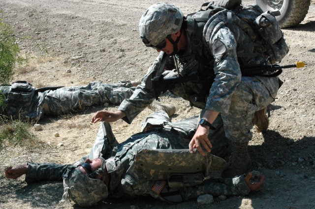 """Cpl. Sam Causley, an infantry Soldier with B Company, 3rd Battalion, 8th Cavalry Regiment, 3rd Brigade Combat Team, 1st Cavalry Division, from Monterey, Calif., assesses a simulated casualty who was injured by an Improvised Explosive Device. This training exercise, part of a two week event that the """"Greywolf"""" brigade conducts to prepare its troops for their upcoming deployment to Iraq, is designed to test the Soldiers' knowledge in combat tactics and first aid."""