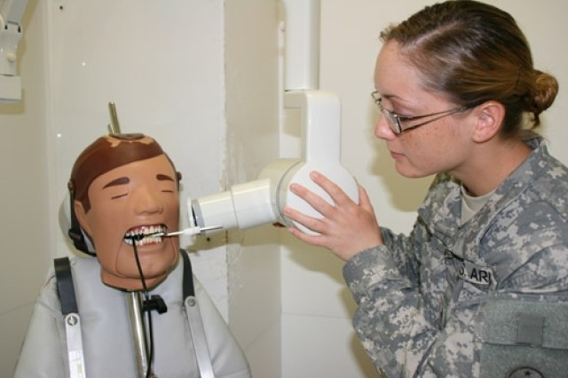 Pfc. Emily Moore sets an X-ray cone position device known as the XCP into the mouth of a manikin for teeth X-rays.""