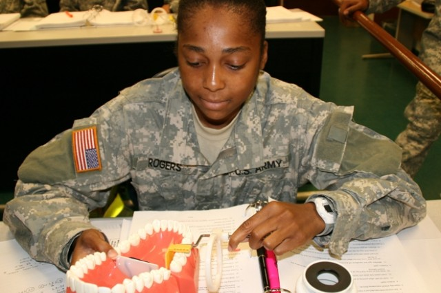 Pfc. Danielle Rogers, C Company, 187th Medical Battalion, studies a set of teeth with an X-ray cone position device during class lecture July 17 at the Dental Specialist Branch, Army Medical Department Center and School. Rogers is a student in the Dental Specialist Course where students learn to assist dentists with materials, X-rays and equipment. ""