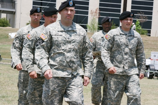 Sgt. Kristopher Biggs (right, front) leads a formation of students during drill and ceremony practice while Staff Sgt. James Hood (right, back), academy instructor, evaluates his performance. Biggs is one of seven Warriors in Transition attending the Army Medical Department NCO Academy for the first time.