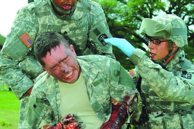 Sgt. Stephen Turner (left) and Pfc. Nicholas Stoup (right), both with the 441st Ground Ambulance Company, carry Maj. Loren Klemp off the battlefield with simulated burn injuries during a training exercise at Fort Hood, Texas.