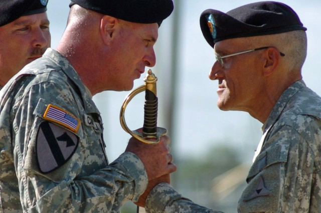 Command Sgt. Maj. Mark Offermann (right) relinquishes the non-commissioned officer's sword to Command Sgt. Maj. Neil Ciotola, the III Corps and Fort Hood command sergeant major, symbolizing his transfer of responsibility of Headquarters Battalion, III Corps, to Command Sgt. Maj. Timothy Livengood at Fort Hood, Texas, July 23.