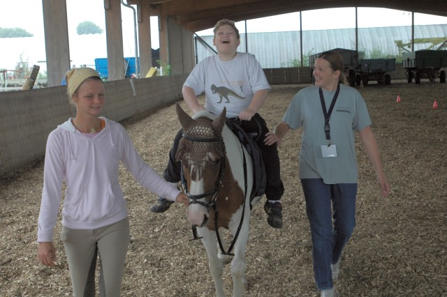A very happy Oisín Oravetz sits astride Gypsy as Carola Wortmann, a riding therapist, and Tracy Jarvis, a care provider, walk with him around a riding pavilion July 17 during the U.S. Army Garrison Heidelberg, Germany, Exceptional Family Member Program's Summer Activity, better known as EFMP camp. Wortmann, who works out of the Wersauer Hof in Reilingen, showed the EFMP camp kids how to take care of and ride a horse.