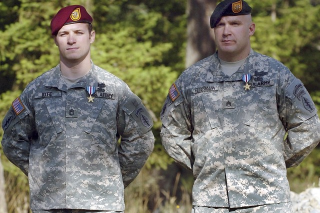 Sergeant 1st Class Chad M. Kite and Staff Sgt. Christopher L. Federmann stand in front of the audience after presentation of their Silver Stars.