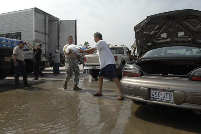 A Soldier from Strike Force 3, part of a Texas Army National Guard task force, gets ice to a victim of Hurricane Dolly at one of 15 distribution points set up throughout the South Texas area.