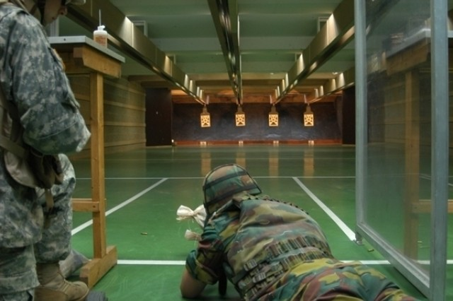 Sgt. Michael Lynch, a military policeman with U.S. Army Garrison Benelux, Belgium, partnered with Belgian 1st Soldier Yves Joine of the 1st Artillery as he fired the M-16 for the first time at the indoor range on ChiAfA..vres Air Base.