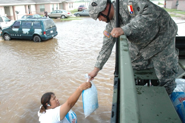 Spc. Timothy C. Berlanga of the Texas Army National Guard hands out a bag of ice to a resident whose neighborhood in Raymondville, Texas was severely flooded July 25 by the deluge of rain from hurricane Dolly.