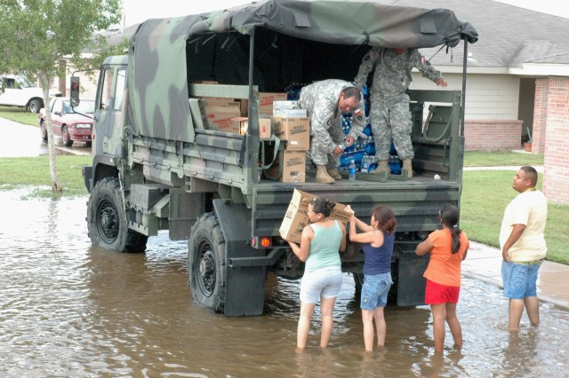 Soldiers of the Texas National Guard distribute food, water and ice July 25 from a light medium tactical vehicle to residents of Raymondville, Texas, flooded by Hurricane Dolly. (