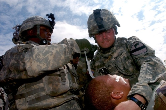 Pfc. Nashone Marbury (left), an HHT medic from Minneapolis, Minn., and Pvt. Michael Johnson, of Cartersville, Ga., work on a casualty during 4th Squadron, 9th Cavalry Regiment, 2nd Brigade Combat Team, 1st Cavalry's Air MEDEVAC at the EMFB site July
