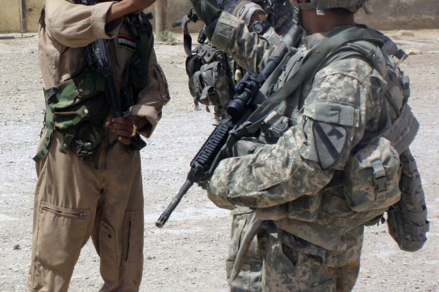 A 2nd Sqdn., 7th Cav. Regt., Soldier and an IA Soldier trade high-fives during a patrol near an IP station in Amarah July 7.