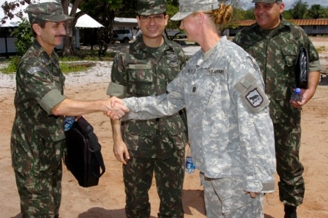 Col. Marcelo Eschiletti from the Brazilian delegation shakes hands with Capt. Sarah Holt, action officer, Task Force Southern Coyote, South Dakota National Guard, during his visit to learn about partnership opportunities similar to Beyond the Horizon 2008 on Saturday, July 19, at Ayoko Kazerne, Suriname.