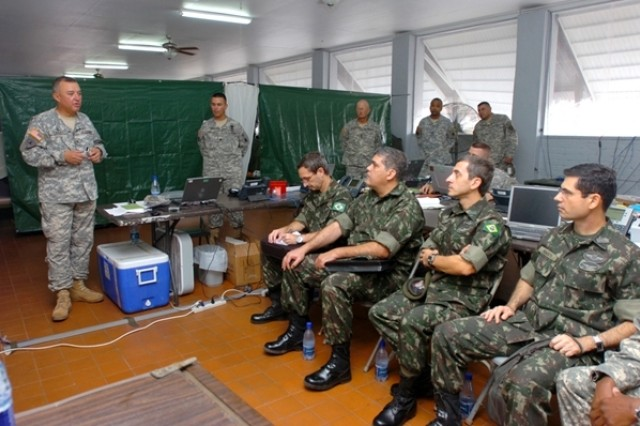 Col. Robert Casias, Beyond the Horizon Task Force commander, U.S. Army South, gives the Brazilian officials a presentation of the Beyond the Horizon 2008 exercise on Saturday, July 19, at Ayoko Kazerne Base Camp in Suriname.
