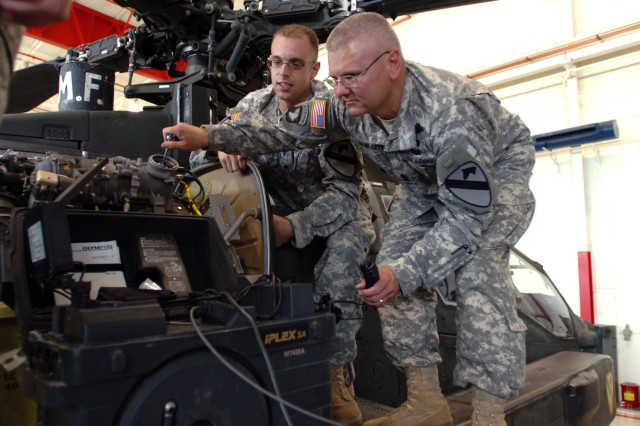 """Buffalo, N.Y., native Sgt. Brett Bolt (left), an aircraft power plant mechanic for Company D, 1st """"Attack"""" Battalion, 227th Aviation Regiment, 1st Air Cavalry Brigade, explains how to inspect the engine blades of an AH-64D Apache attack helicopter to Command Sgt. Maj. Malloy (right), the command sergeant major for the 1st Cavalry Division, during his visit to the 1-227th hangar on Robert Gray Army Air Field, Fort Hood, Texas, July 25. The inspection process is called an engine bore scope and it was just one of many things Malloy tried his hand at during his visit."""
