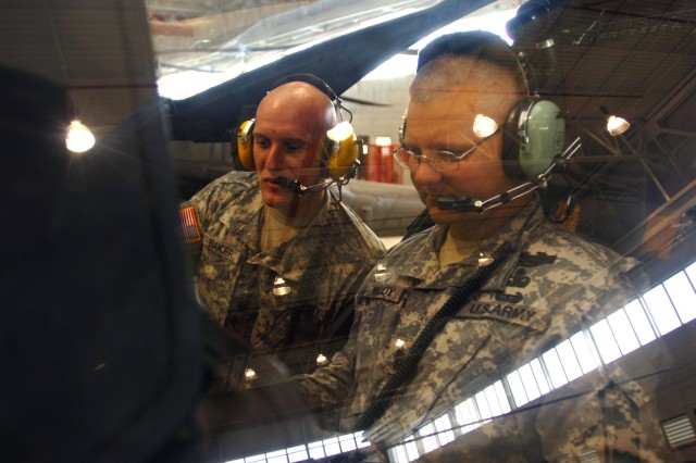 """Hesperia, Calif., native Spc. Joseph Baker (left), an armament specialist for Company D, 1st """"Attack"""" Battalion, 227th Aviation Regiment, 1st Air Cavalry Brigade, 1st Cavalry Division, shows Command Sgt. Maj. Rory Malloy (right), command sergeant major of the 1st Cav. Div., some of the controls of an AH-64D Apache attack helicopter during his visit to the 1-227th hangar on Robert Gray Army Air Field, Fort Hood, Texas, July 25. Malloy plans to visit his brigades throughout the First Team to understand what the troopers daily operations are like, he said."""