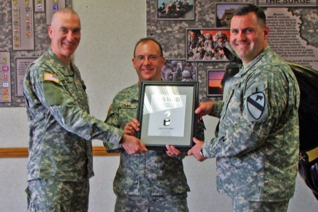 Maj. Gen. Daniel Bolger (left) presents the Telly Award to Cookeville, Tenn. native, Staff Sgt. Jon Cupp (middle) and Dale City, Va. native Maj. Randall Baucom, officer in charge of Public Affairs for 1st Brigade Combat Team, 1st Cavalry Division.  The award was for video production and broadcast excellence in a ceremony held at the 1st Cavalry Division headquarters July 22.