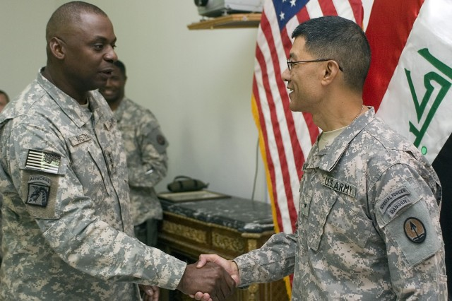 Lt. Gen. Lloyd J. Austin III, commander, Multi-National Corps - Iraq, congratulates Brig. Gen. Joseph Caravalho Jr., Multi-National Force - Iraq and MNC- I surgeon, during a promotion ceremony held in Caravalho's honor July 28 at the Al-Faw Palace, Camp Victory, Baghdad.  Caravalho's family was on hand to witness the promotion via video teleconference from Fort Bragg, North Carolina.