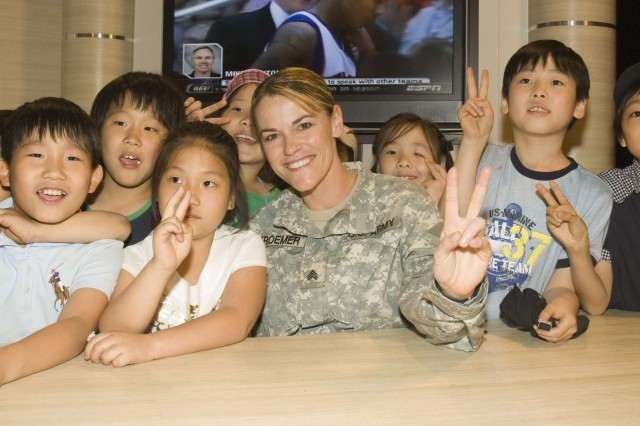 Korean elementary school children pose with broadcaster Sgt. Joy Kroemer of American Forces Network-Korea during a children's day tour at Yongsan. The garrison frequently welcomes Korean nationals on post as part of the Good Neighbor program.