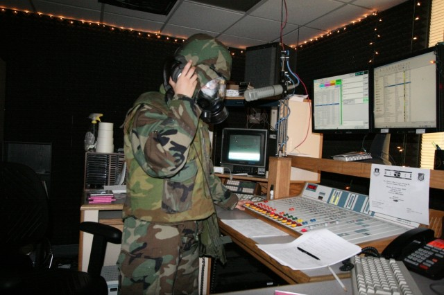 Air Force Staff Sgt. Rachael Herrmann, a broadcast producer, wears-NBC protective equipment while providing music over the airwaves to Osan Air Base servicemembers during an exercise.