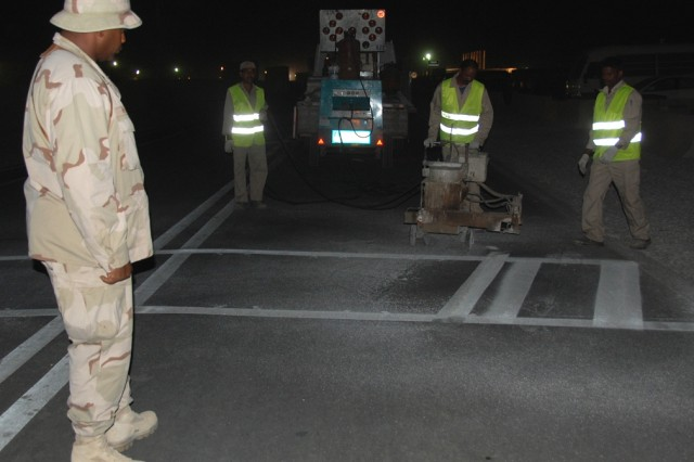 Under the watchful eye of Petty Officer First Class Frankie Presley, a Utilitiesman with Naval Mobile Construction Battalion 74, contractors paint a crosswalk on South Carolina Road, Friday evening, July 25, 2008, at Camp Arifjan, Kuwait.  According to Presley, the painting of crosswalks is the last major step in the paving project which fronts the Army Materiel Command housing area in Zone 6.