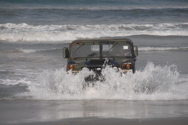 A Soldier drives a Humvee through the Pacific surf during JLOTS. JLOTS is designed to move large amounts of equipment and supplies from the ocean to the beach without a fixed port.