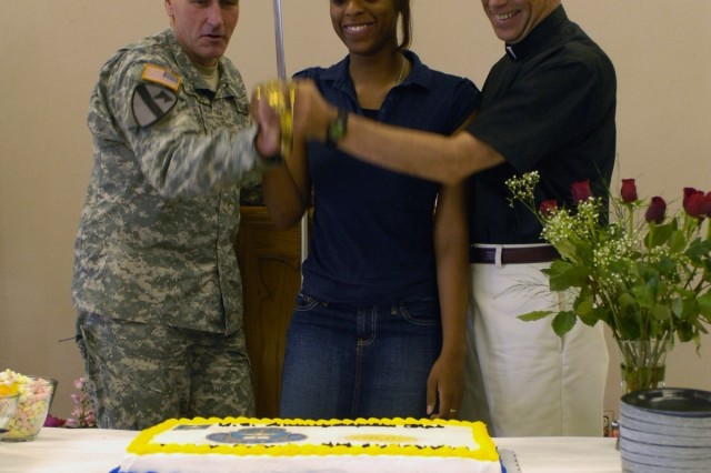 Kenton, Ohio native, Col. John M. Murray (left), acting deputy commanding general for maneuver, 1st Cavalry Division; Killeen, Texas native Tiffanee Roach (center), chaplain assistant 504th Brigade Support Battalion, and III Corps Chaplain Col. Michael T. Lembke (right), from Crawfordsville, Ind., make the ceremonial first cut to the cake during Fort Hood's 233rd year remembrance ceremony luncheon at Comanche Chapel, July 25.