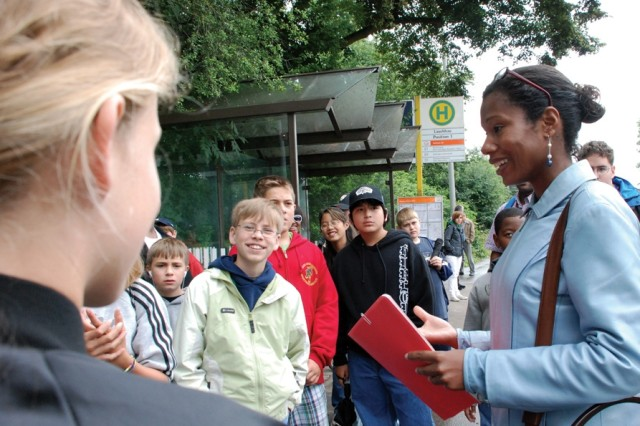 Angie Collins, right, the Child and Youth Services Teen Stuttgart Newcomer Orientation coordinator, quizzes teens on how they would order certain menu items in German while waiting for the bus outside Patch Barracks July 18.