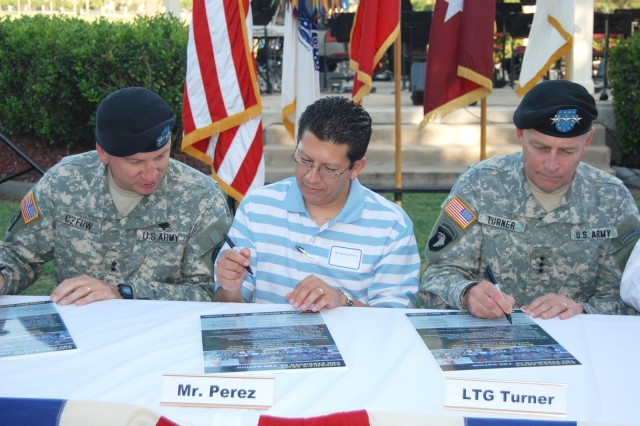 (From left) Maj. Gen. Russell Czerw, commanding general, Fort Sam Houston and Army Medical Department Center and School; Richard Perez, president, Greater San Antonio Chamber of Commerce; and Lt. Gen. Thomas Turner, commanding general, Army North, sign the Army Community Covenant during a ceremony July 27 in front of the gazebo on Staff Post Road.