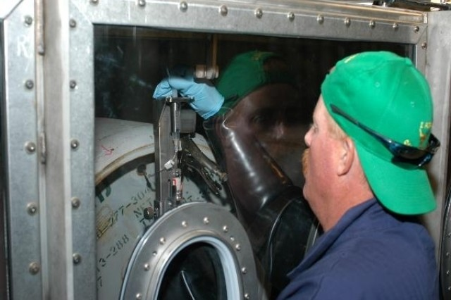 A TOCDF worker reaches inside a glove box to draw a sample of mustard agent from a ton container.