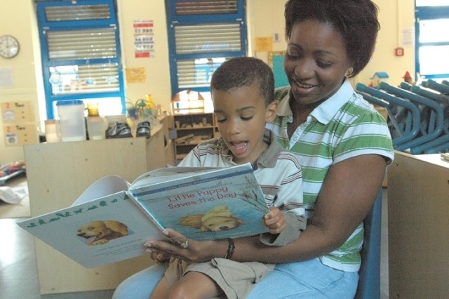 "Patricia Robinson holds Aaron Blakeney as they look through ""Little Puppy Saves the Day,"" and work on animal sounds July 24 in a pre-school classroom at the Patrick Henry Village Child Development Center. Robinson is a respite care provider who comes to Blakeney\'s classroom daily during his classmates' naptime. Blakeney choses not to sleep during these times, and Robinson works with him in various areas."